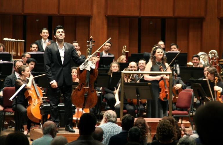 """Kian Soltani, left, who plays on a 1680 cello by the Grancino brothers, and violist Miriam Manasherov stand after playing solos in Richard Strauss's """"Don Quixote"""" at the John F Kennedy Center for the Performing Arts in Washington on November 7, 2018"""