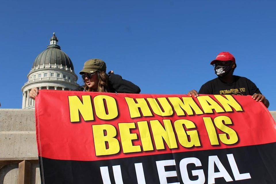 """Activist Ma Black helps rally organizer Natasha Cadet put up a banner emblazoned with the message """"No human being is illegal"""" at the Utah Capitol grounds. (Enrique Limón)"""