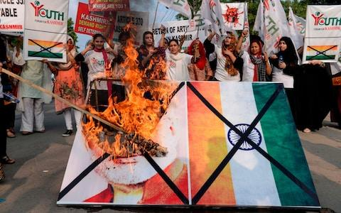 <span>Activists of the 'Youth Forum for Kashmir' group shout slogans as they burn a picture of Indian Prime Minister Narendra Modi in Lahore</span> <span>Credit: AFP </span>