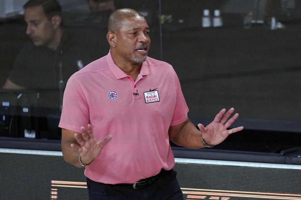 """FILE - In this Sept. 15, 2020, file photo, Los Angeles Clippers head coach Doc Rivers questions a call during the first half of an NBA conference semifinal playoff basketball game against the Denver Nuggets in Lake Buena Vista, Fla. Rivers is now head coach of the Philadelphia 76ers. The first preseason camps of the coronavirus era are formally open, with teams limited for now to individual sessions with one coach and one player at one basket, all of this starting to happen as the pandemic continues raging and more and more Americans are testing positive. """"I'm very concerned if we can pull this off,"""" Philadelphia coach Doc Rivers said. (AP Photo/Mark J. Terrill, File)"""
