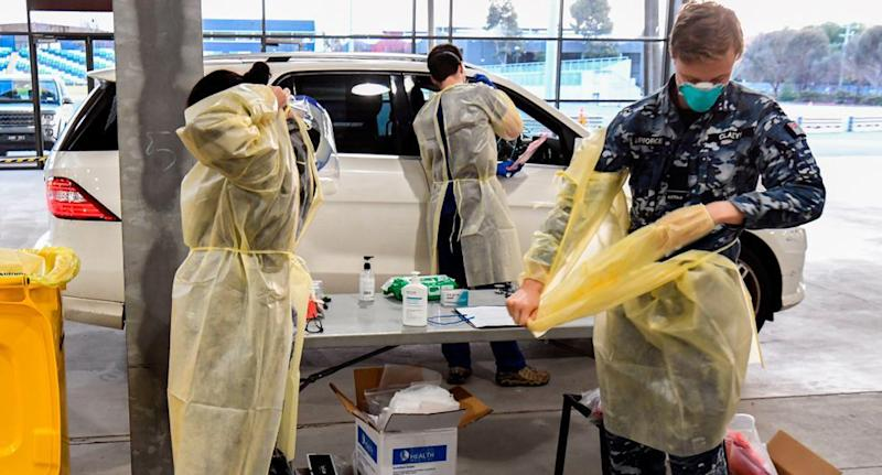 An Australian Defence Force member and two other healthcare workers in PPE at a Melbourne coronavirus test station.