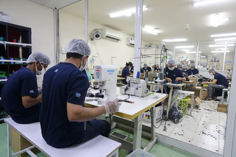 Workers make face masks at a factory, following the outbreak of COVID-19, in Ajman
