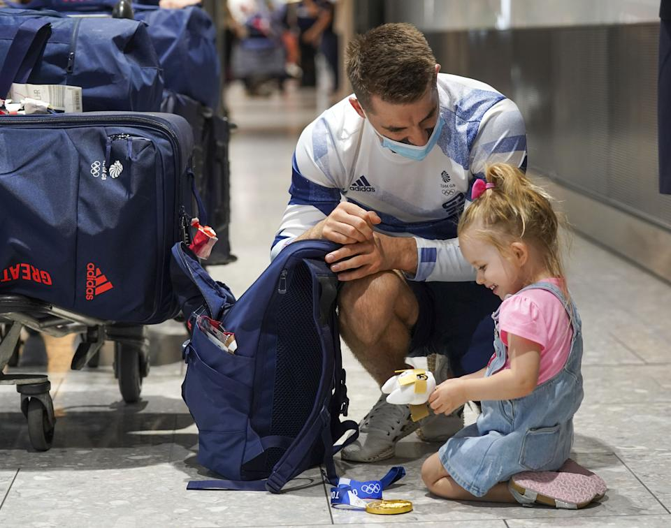 Olympic gymnast Max Whitlock with his daughter Willow as he arrives back at London Heathrow Airport from the Tokyo 2020 Olympic Games. Picture date: Tuesday August 3, 2021.