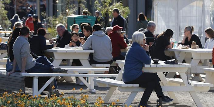 Customers enjoy lunch in the sunshine at the Riverside Market in Christchurch, New Zealand, Sunday, Aug. 9, 2020.