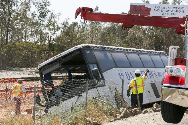 Salvage towing crews remove an overturned tour bus carrying gamblers to a casino on the 210 Southern California freeway injuring more than 50 people on board in Irwindale, Calif., on Thursday, Aug. 20, 2013. The bus went through a chain-link fence off the side of the road and ended up on its side down a dirt embankment between the freeway and railroad tracks. (AP Photo/Damian Dovarganes)