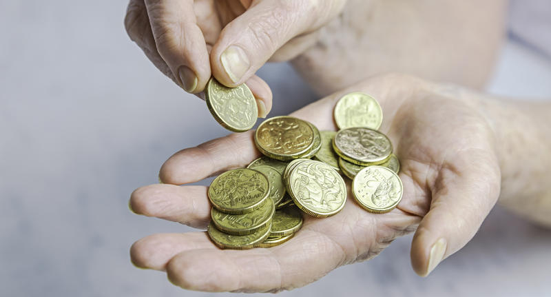 Close-up of senior female hands counting one and two dollar coins in hand. Selective focus, horizontal, marble background.