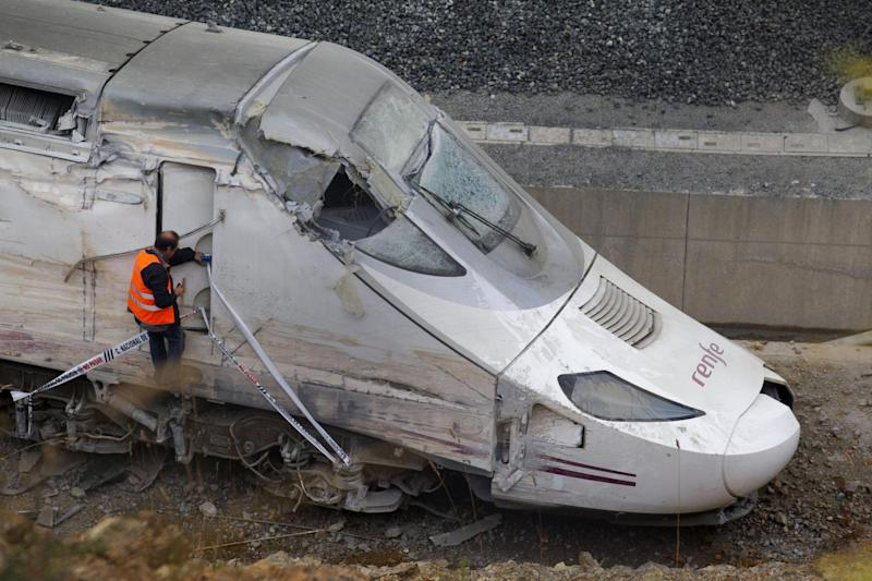"""FILE - In this July 25, 2013 file photo, a rail personnel worker checks the cabin of a derailed train following an accident in Santiago de Compostela, Spain. A Spanish court official said Monday July 29, 2013 that judicial police would soon begin extracting information from the """"black box"""" of a train that crashed last week killing 79 people and injuring some 130 in the country's worst train accident in decades. It is hoped the box might establish what happened in the final seconds prior to the crash. The investigation has increasingly focused on why the driver failed to brake in time to stop the train from hurtling into a dangerous curve, where it careered off the tracks and slammed into a concrete wall. On Monday, Spain's royal family and leading politicians were to attend a somber Mass in homage to the victims killed and injured. (AP Photo/Lalo R. Villar)"""