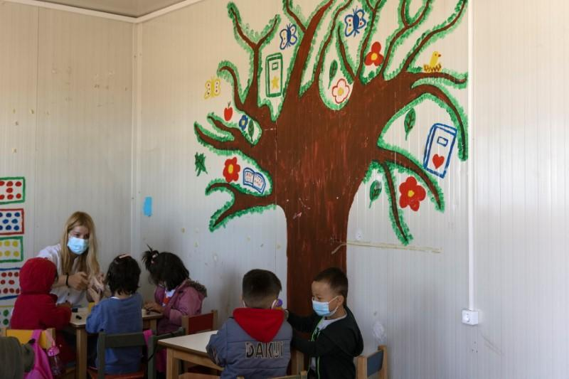 Children attend a class at a school in the Ritsona camp for refugees and migrants