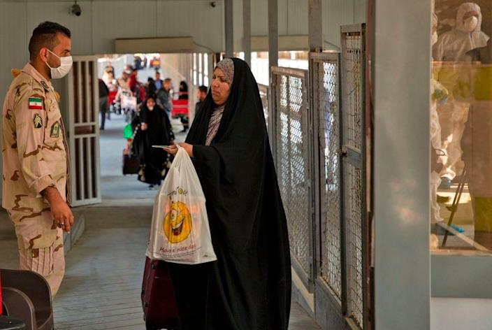 "An Iraqi traveler shows her passport to an Iranian officer at the Shalamjah border crossing, some 15 kilometers southeast of the city of Basra, upon their return from Iran on Feb. 21, 2020. Iran reported two more deaths among 13 new cases of coronavirus in the Islamic republic, bringing the total number of deaths to four and infections to 18. Following the announcement, Iraq clamped down on travel to and from the Islamic republic. The health ministry in Baghdad said people from Iran had been barred from entering Iraq ""until further notice""."
