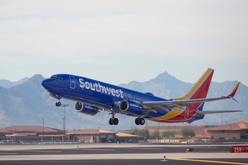 A Southwest Airlines plane taking off, with mountains in the background