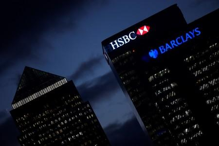 HSBC and Barclay's buildings are lit up at dusk in the Canary Wharf financial district of London