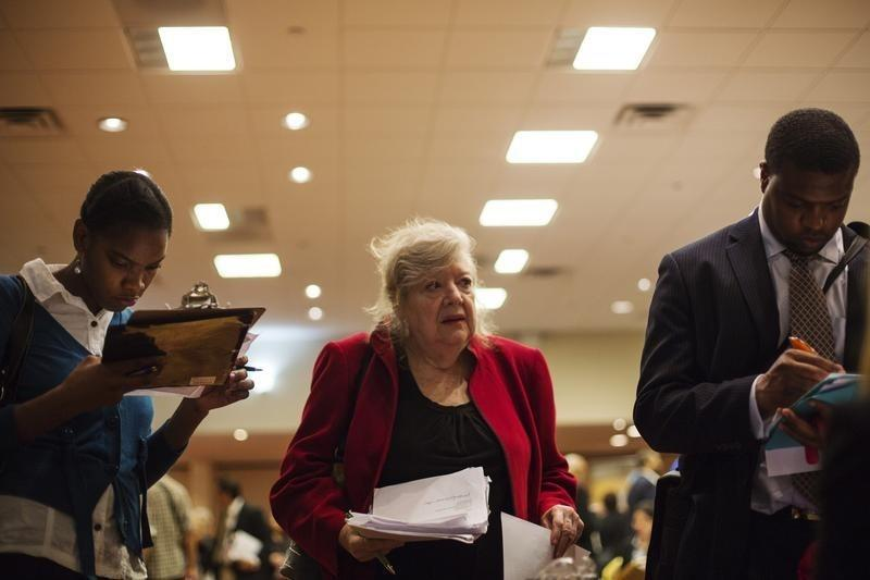 Job seekers fill out job applications for recruiters as they attend a job fair in New York