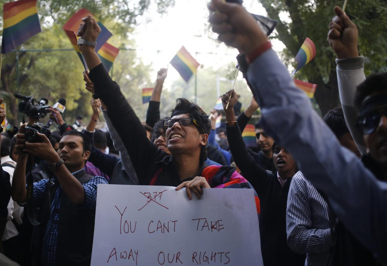 "Gay rights activists wave flags and shout slogans as they attend a protest against a verdict by the Supreme Court in New Delhi December 11, 2013. India's Supreme Court on Wednesday reinstated a ban on gay sex in the world's largest democracy, following a four-year period of decriminalisation that had helped bring homosexuality into the open in the socially conservative country. In 2009 the Delhi High Court ruled unconstitutional a section of the penal code dating back to 1860 that prohibits ""carnal intercourse against the order of nature with any man, woman or animal"" and lifted the ban for consenting adults. The Supreme Court threw out that decision, saying only parliament could change Section 377 of the penal code, widely interpreted to refer to homosexual sex. Violation of the law can be punished with up to 10 years in jail. REUTERS/Anindito Mukherjee (INDIA - Tags: CRIME LAW SOCIETY)"