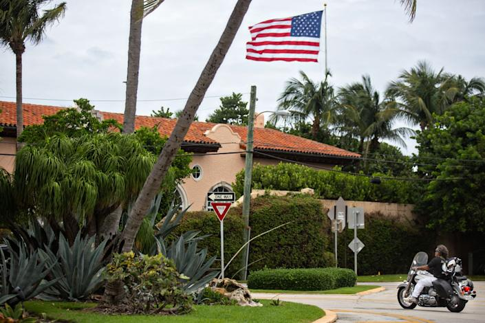 A large U.S. flag flies over Mar-a-Lago Club, seen from the street.