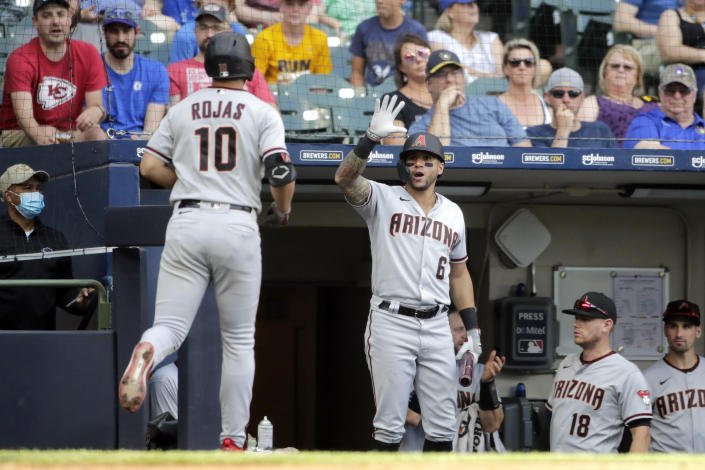 Arizona Diamondbacks' Josh Rojas (10) is congratulated at the dugout by David Peralta (6) after hitting a solo home run during the sixth inning of a baseball game against the Milwaukee Brewers, Saturday, June 5, 2021, in Milwaukee. (AP Photo/Aaron Gash)