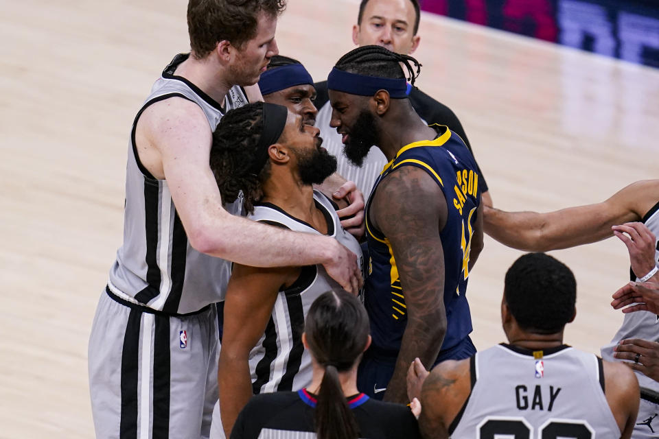 Indiana Pacers forward JaKarr Sampson (14) and San Antonio Spurs guard Patty Mills (8) exchange words during the second half of an NBA basketball game in Indianapolis, Monday, April 19, 2021. (AP Photo/Michael Conroy)
