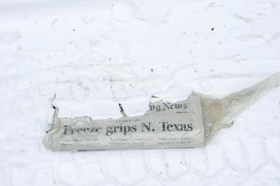 <p>A newspaper with the headline 'Freeze Grips N. Texas' is seen buried in snow in McKinney, Texas, on Feb. 16. </p>