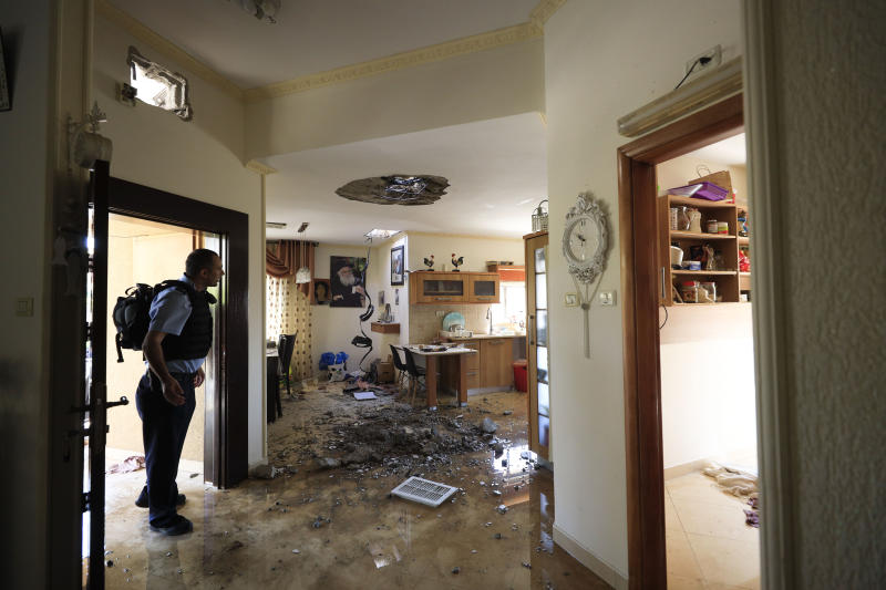 A policeman check the damage to a house hit by a rocket fired from Gaza Strip in Netivot, Israel, after it was hit by a rocket fired from Gaza Strip, Tuesday, Nov. 12m 2019. Israel has killed a senior Islamic Jihad commander in Gaza in a rare targeted killing that threatened to unleash a fierce round of cross-border violence with Palestinian militants. (AP Photo/Tsafrir Abayov)