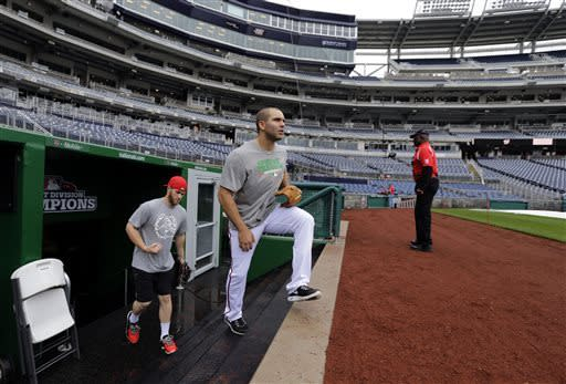 Washington Nationals left fielder Bryce Harper, left, and second baseman Danny Espinosa walk out of the clubhouse to throw before an interleague baseball game against the Detroit Tigers was rained out, at Nationals Park Tuesday, May 7, 2013, in Washington. They have rescheduled the game for Thursday May 9 at 4:05 pm. (AP Photo/Alex Brandon)