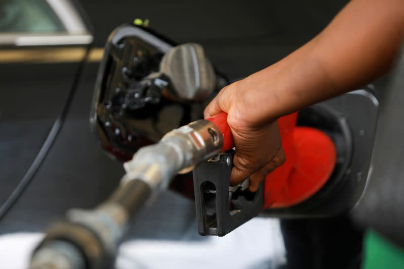 FILE PHOTO: A gas station attendant pumps fuel into a customer's car at the NNPC Mega petrol station in Abuja