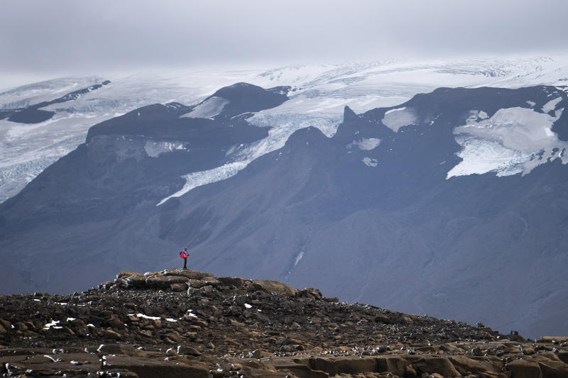 A man stops on his way to the top of what once was the Okjokull glacier, in Iceland, Sunday, Aug. 18, 2019. With poetry, moments of silence and political speeches about the urgent need to fight climate change, Icelandic officials, activists and others bade goodbye to the first Icelandic glacier to disappear. (AP Photo/Felipe Dana)