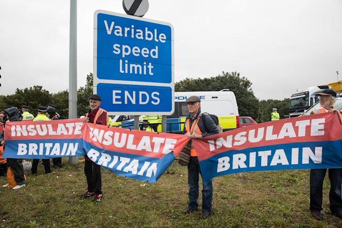 Insulate Britain climate activists hold banners after a M25 slip road at Junction 14 close to Heathrow airport was blocked as part of a campaign intended to push the UK government to make significant legislative change to start lowering emissions on 27th September 2021 in Colnbrook, United Kingdom. The activists are demanding that the government immediately promises both to fully fund and ensure the insulation of all social housing in Britain by 2025 and to produce within four months a legally binding national plan to fully fund and ensure the full low-energy and low-carbon whole-house retrofit, with no externalised costs, of all homes in Britain by 2030. (photo by Mark Kerrison/In Pictures via Getty Images)