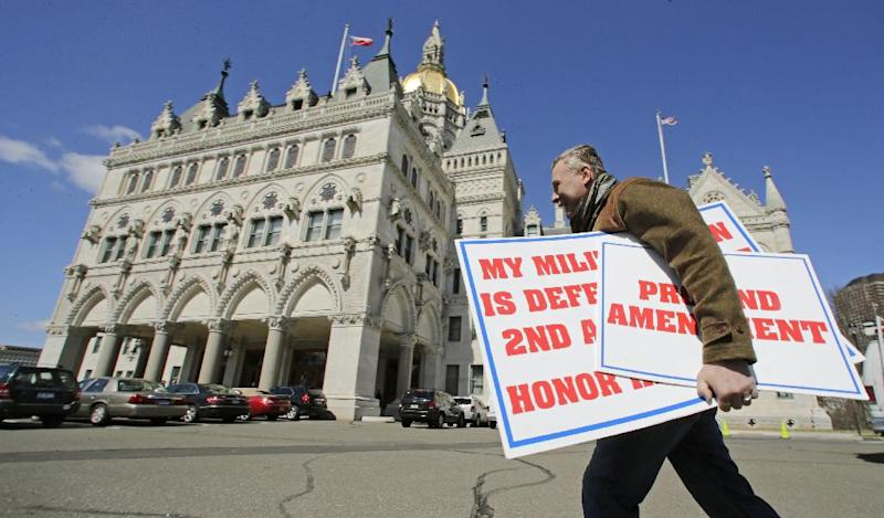 Jody Winslow, of Farmington, Conn., carries signs regarding the second amendment of the U.S. Constitution as he heads back to the Capitol in Hartford, Conn., Wednesday, April 3, 2013. Hundreds of gun rights advocates are gathering at the statehouse in Hartford ahead of a vote in the General Assembly on proposed gun-control legislation. (AP Photo/Charles Krupa)