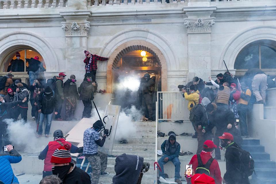 Security forces combat rioters with tear gas at the Capitol, January 6, 2021.