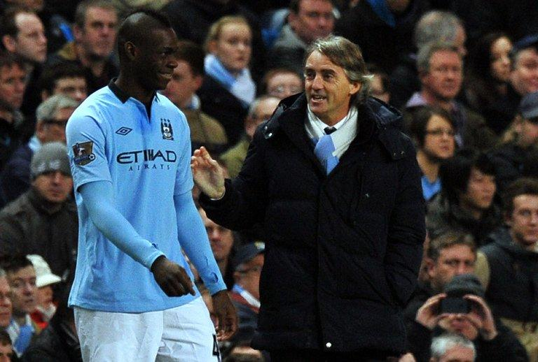 Mario Balotelli (L) shares a joke with Roberto Mancini when coming on as a substitute on January 5, 2013