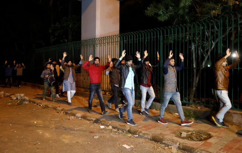 Students raising their hands leave the Jamia Milia University following a protest against a new citizenship law, in New Delhi