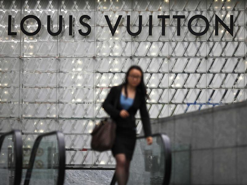 woman walking under Louis Vuitton sign in China