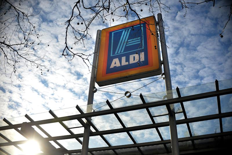 The photo shows an Aldi sign with a cloudy sky in the background. Source: AAP