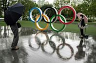 Rail falls as people walk past the Olympic rings near the National Stadium, main venue for the Tokyo 2020 Games, on June 23, 2021