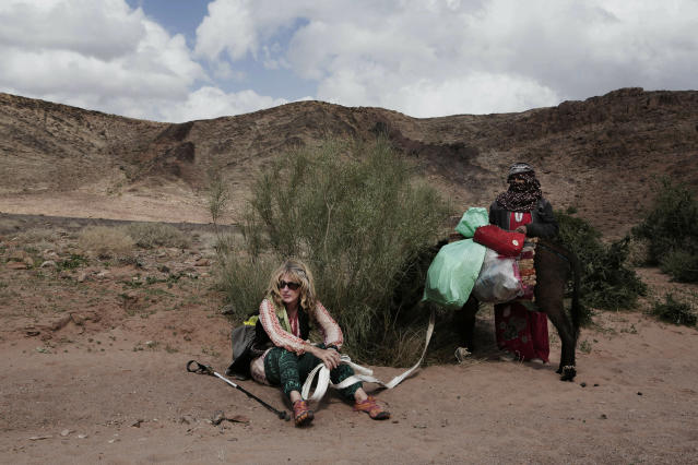 In this March 30, 2019 photo, Julie Patterson, a Sinai Trail trip officer rests with guide Umm Yasser, on a trek in the mountains, near Wadi Sahw, Abu Zenima, in South Sinai, Egypt. Umm Yasser is breaking new ground among the deeply conservative Bedouin of Egypt's Sinai Peninsula. Women among the Bedouin almost never work outside the home, and even more rarely do they interact with outsiders. But Umm Yasser is one of four women from the community who for the first time are working as tour guides as part of Sinai Trail. (AP Photo/Nariman El-Mofty)