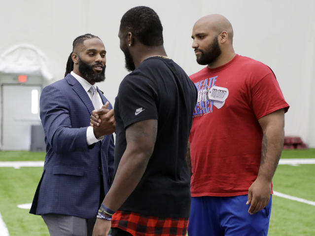 Former Tennessee Titans safety Michael Griffin, left, talks with linebacker Brian Orakpo, center, and defensive end DaQuan Jones, right, after Griffin signed a one-day contract with the team and then retired as a Titan Monday, May 7, 2018, in Nashville, Tenn. Griffin, a first-round pick by the Titans in 2007, played nine seasons for Tennessee. (AP Photo/Mark Humphrey)