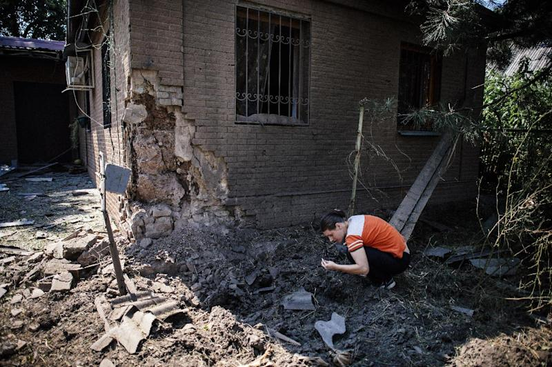 A woman collects shrapnels after a shelling in Donetsk on August 14, 2014 (AFP Photo/Dimitar Dilkoff)