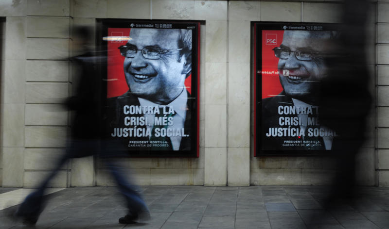 People walk below posters of President of the Catalunya Generalitat regional government Jose Montilla  in Barcelona, Spain, Tuesday, Nov. 23, 2010. Spain's ruling Socialists look set to be booted from office in elections this weekend in the powerful northeastern region of Catalonia in what could be the first of a series of punishments in the coming months for their handling of the nation's economic crisis. Up for grab in Sunday's ballot are 135 seats in the local parliament where the Socialists, now headed by regional government President Jose Montilla, have governed for the past two terms in coalition with the pro-independence Republican Left of Catalonia and the Catalan Green Initiative.  (AP Photo/Manu Fernandez)