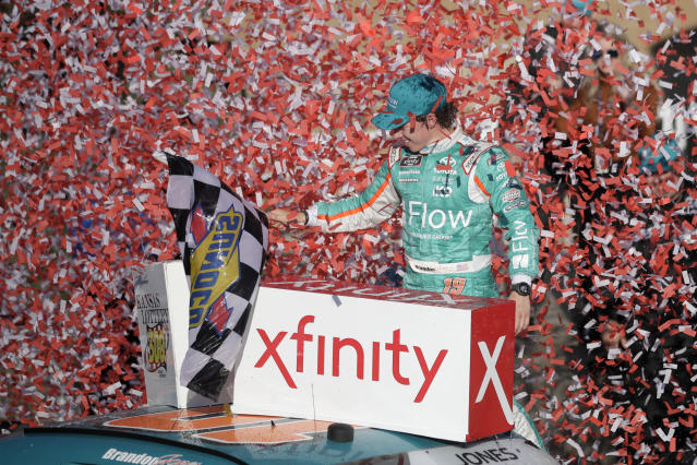 """FILE - In this Oct. 19, 2019, file photo, Brandon Jones celebrates in Victory Lane after winning a NASCAR Xfinity Series auto race at Kansas Speedway in Kansas City, Kan. NASCAR has signed Busch Beer, Coca-Cola, Geico and Xfinity as its premier partners"""" in a change to its traditional sponsorship model. The premier series starting next year will be known as the NASCAR Cup Series and not feature a title sponsor. (AP Photo/Orlin Wagner, File)"""