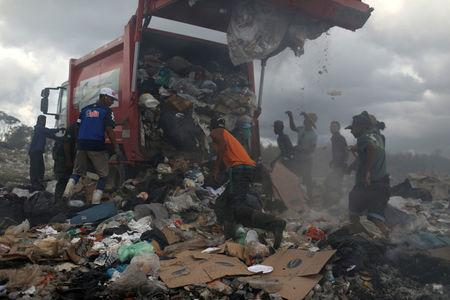 Venezuelan migrants wait while the rubbish truck unload at the garbage dump in the border city of Pacaraima