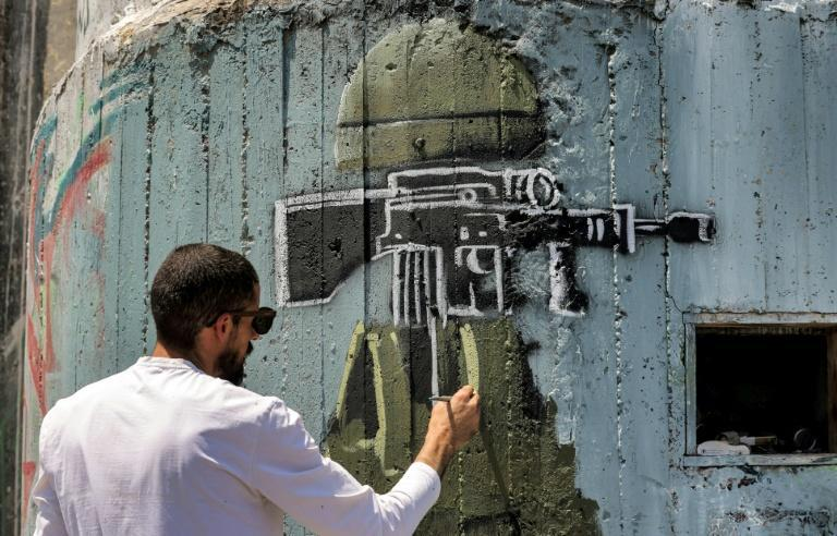 Palestinian artist Taqi Spateen paints a mural depicting a sniper rifle underneath Jerusalem's Dome of the Rock mosque compound