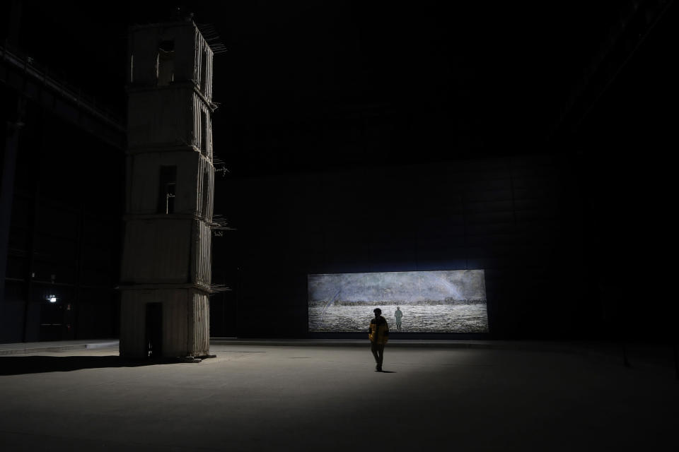 A visitor walks through Anselm Kiefer's art installation 'The Seven Heavenly Palaces', on display at the Hangar Bicocca museum, in Milan, Italy, Wednesday, Feb. 3, 2021. Hangar Bicocca museum reopened Wednesday following the easing of COVID-19 restriction measures. (AP Photo/Luca Bruno)