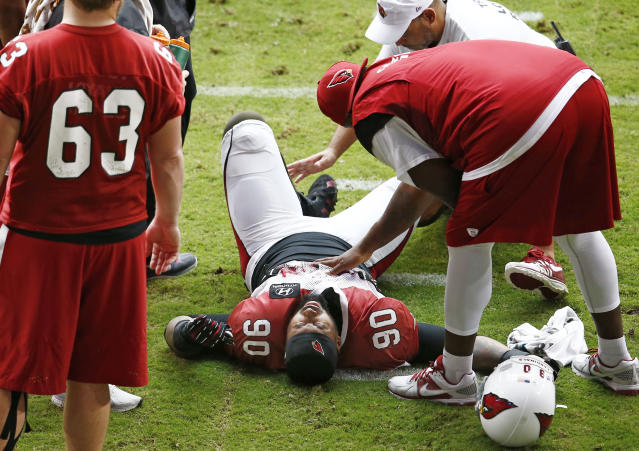 Arizona Cardinals defensive end Darnell Dockett is atended while down in pain during NFL football training camp Monday, Aug. 18, 2014 at University of Phoenix Stadium in Glendale, Ariz. Dockett left the field on a cart. (Photo by Rob Schumacher/The Arizona Republic) (AP Photo/The Arizona Republic, Rob Schumacher)
