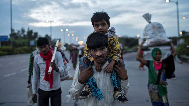 A migrant worker carries his son as they walk along a road with others to return to their village