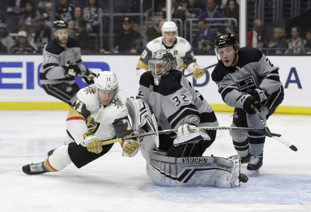 Los Angeles Kings goaltender Jonathan Quick, center, deflects a shot in front of Vegas Golden Knights' William Karlsson, left, during the first period of an NHL hockey game Saturday, Dec. 29, 2018, in Los Angeles. (AP Photo/Marcio Jose Sanchez)