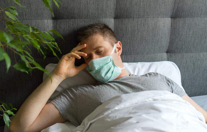 Sick man with medical mask lying in bed. Coronavirus quarantine concept.
