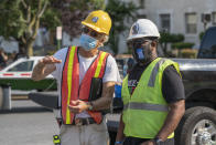 In this photo provided by Sanjay Suchak, Richmond sculptor Paul DiPasquale, left, talks with Devon Henry during the removal of the J.E.B. Stuart statue on Monument Avenue on Tuesday July 7, 2020 in Richmond, Va. Henry's company won the contract to remove the Confederate Statues from the city of Richmond. (Sanjay Suchak via AP)