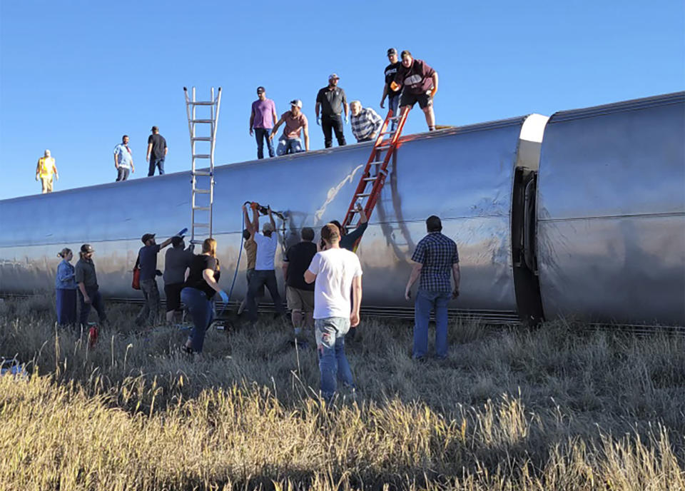 In this photo provided by Kimberly Fossen people work at the scene of an Amtrak train derailment on Saturday, Sept. 25, 2021, in north-central Montana. Multiple people were injured when the train that runs between Seattle and Chicago derailed Saturday, the train agency said. (Kimberly Fossen via AP)