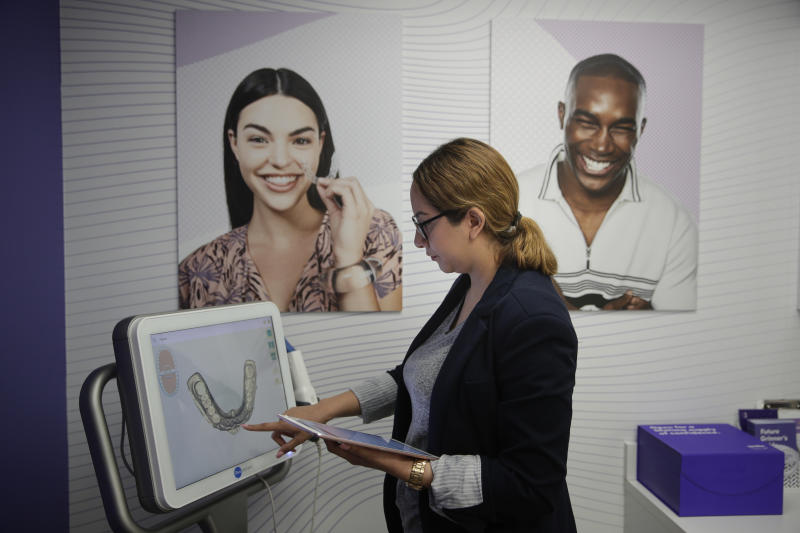 Dental assistant Jessica Buendia looks at a scanned image of patient's teeth in SmileDirectClub's SmileShop located inside a CVS store Wednesday, April 24, 2019, in Downey, Calif. CVS Health is venturing into dental care with plans to offer the relatively new teeth-straightening service. (AP Photo/Jae C. Hong)