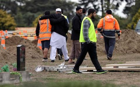Muslims embrace after overseeing the excavating of graves at a Muslim cemetery in Christchurch, New Zealand - Credit: AP