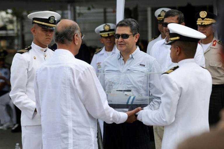 Honduran President Juan Orlando Hernandez (center with sunglasses) takes part in a ceremony marking the arrival of a warship bought from Israel